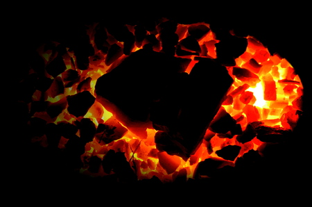 Burning coals of anthracite of different fractions on a black background.