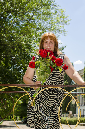 Woman with a bouquet of red flowers.