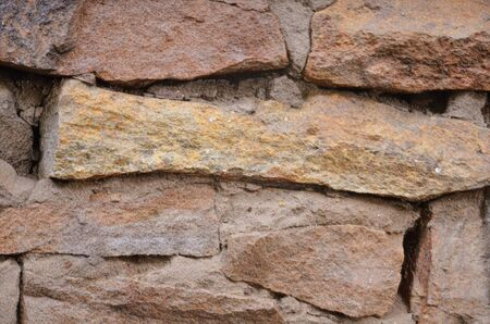 The background consists of a masonry wall with a large die.