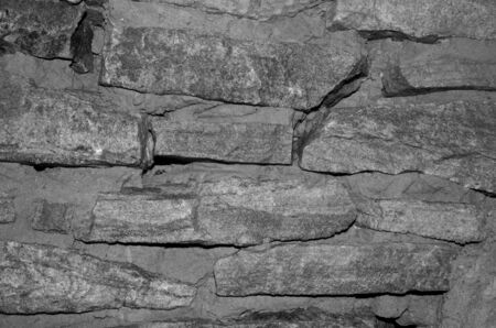 Masonry stone wall is covered with black and white.