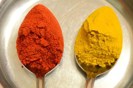 Two metal spoons with spices of different colors.