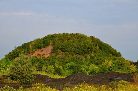 The landscape consists of a burnt mine waste heap, sheltered by green vegetation and heaps of coal sludge.