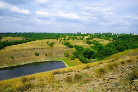 Natural countryside landscape overlooking a small pond and rolling hills. Zdjęcie Seryjne