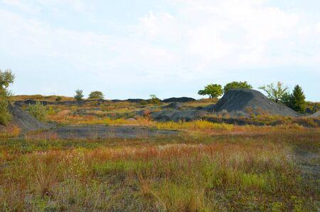 Mine rock lies among the natural landscape.