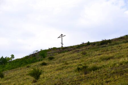 A wooden cross stands on top of a mountain. Zdjęcie Seryjne