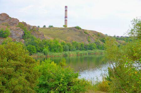 The landscape consists of a picturesque pond, rocks and a concrete pipe enterprise.