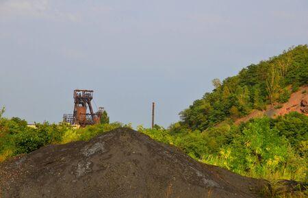 Coal mine hoisting machines amid the masses of a coal mine and heap. Stock Photo