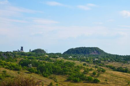 A relief terrain overlooking a small village and a coal-mining mine on the horizon.