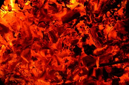 Burning coal mixed with wood as a background.