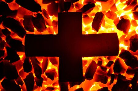 A metal cross is heated on anthracite coal.