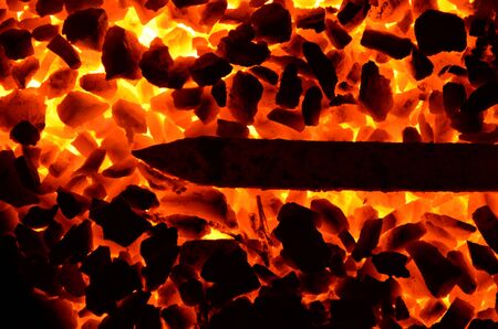 A sharp metal rod is heated on anthracite coal.