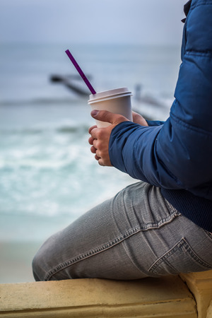 warms: man warms his hands with cup of takeaway coffee. Sea is on background.
