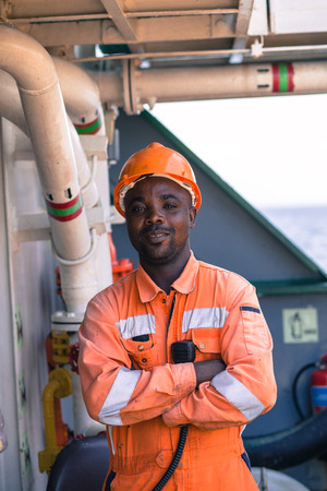 seaman:  young african seaman standing on deck dressed in coverall and safety helmet with VHF radui station waiting for work orders Stock Photo