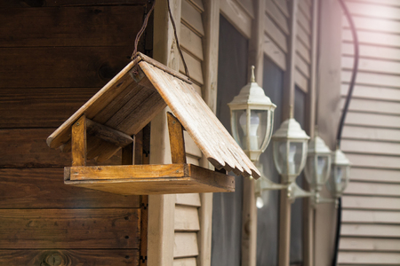 Opened birdhouse mounted on the wall of wooden house, waiting for birds to come. beautiful lanterns with bulbs behind