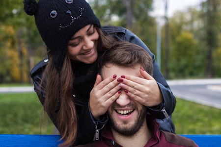 he she: Closeup shot of young beautiful laughing stylish couple in autumn park. They look happy. She is kissing him. He has a beard. She has a piercing in the nose. She wears black hat with bubo.