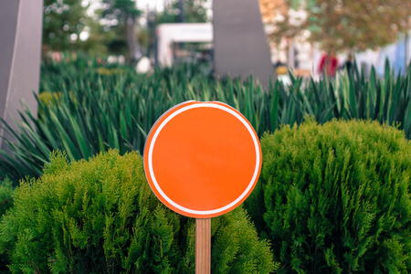 orange sign: Empty round orange sign with green long plants on the background Stock Photo