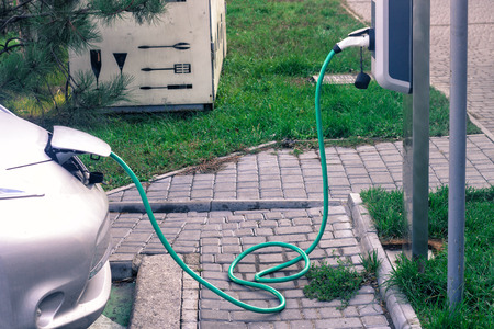 Stromversorgung für das Laden von Elektroautos. Ladestation für Elektroautos. Nahaufnahme der Stromversorgung, die in ein geladenes Elektroauto eingesteckt wurde. Standard-Bild