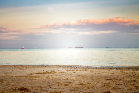 Seascape view from shore during sunset. Ships  are on horizont