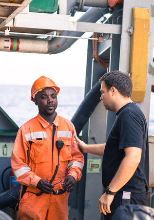 friendship of nations on board of ship/vessel. European Chief officer instructing African seaman on deck before job.