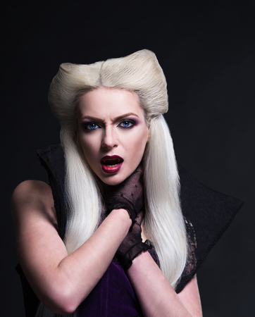 Beautiful blonde girl vampire is strangling herself and showing teeth. Studio photo with black background