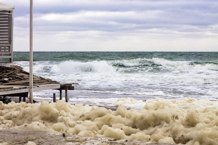 destructive: lot of sea foam and powerful sea splash wave with sprays and destructive effects of the storm on the coast Stock Photo