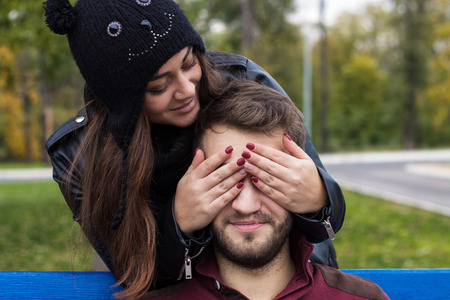he she: Closeup shot of young beautiful stylish couple in autumn park. She closes his eyes. He has a beard. She has a piercing in the nose. She wears black hat with bubo. Stock Photo