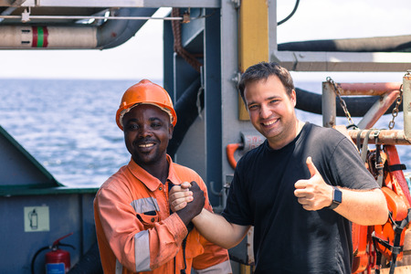 friendship of nations on board of ship/vessel. African seaman and European Chief Mate smiling and shaking hands on deck. Stock Photo