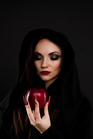 poisoned: Stepmother witch watching at poisoned red apple