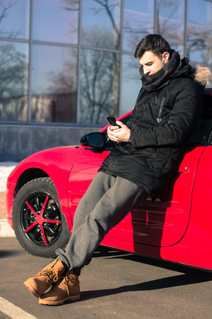 young man phoning near modern red sport car
