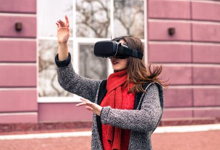 virtual reality headset, VR glasses, VR goggles - beautiful young girl with virtual reality headset or 3d glasses  posing on the street interested by 360 image Stock Photo