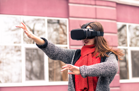 virtual reality headset, VR glasses, VR goggles - beautiful young girl playing with virtual reality headset or 3d glasses  on the street interested by 360 image