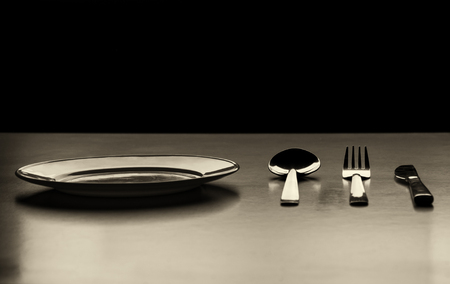 Empty plate with spoon, knife and fork on a black background. low key picture