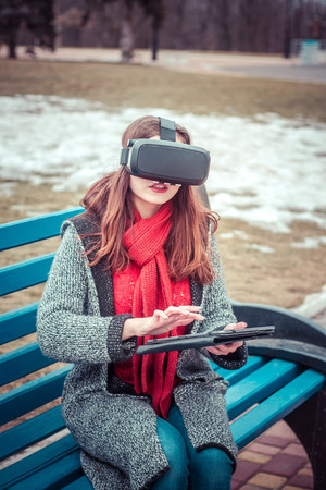 beautiful young girl with virtual reality VR headset  and tablet on the street interested by 360 image. Connection VR with tablet