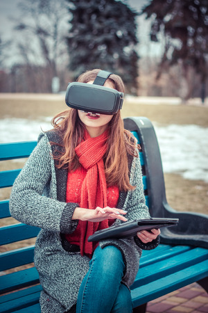 beautiful young girl with virtual reality VR headset on the street interested by 360 image