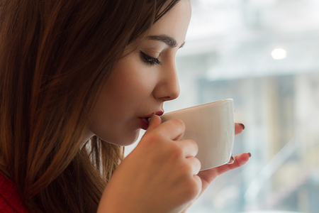 smal:  Young girl drinks tea from  smal cup in cafe with big window
