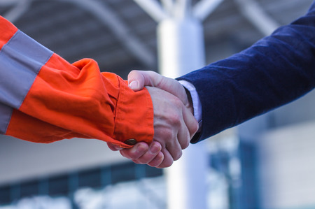 businessman handshaking with worker. Handshake of suit and boilersuit. Business modern background