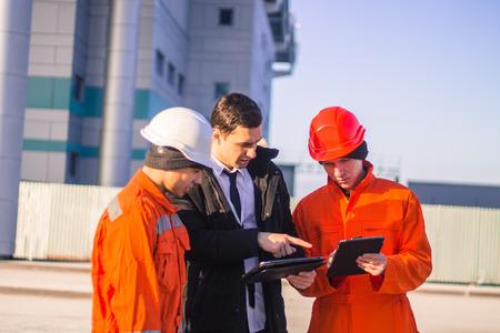 Patron ou Chef instruit une jeune équipe de jeunes ingénieurs avec un projet de construction sur tablette. Technologie au travail. Contexte moderne d'affaires