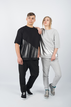Fashion girl  leans on boys shoulder. Young muscular man wearing black clothes and sneakers with girl in grey clothes solated on white background