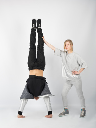 Cheerful couple having fun posing in studio. He stands on his hands and she arched her body and lifted her leg upward.