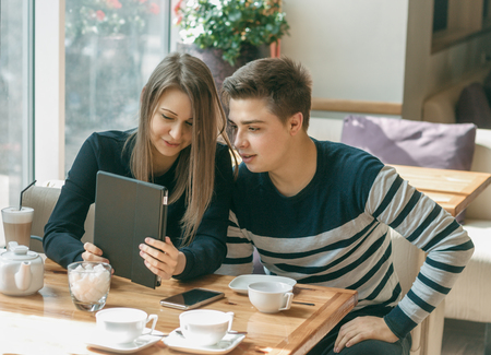 they are watching: Cheerful couple dating in a cafe. They are having fun and watching.