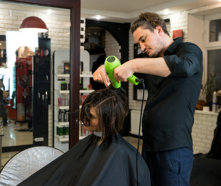 coiffeur: The hairdresser dries hair of Beautiful woman with a hairdryer. He is preparing for haircut in the beauty salon.