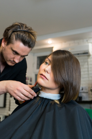 coiffeur: Male hairdresser does a haircut to pretty woman in the beauty salon.