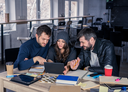 they are watching: Young smart team. Group of  modern people watching project on tablet in the office. Working environment with laptop, coffee, notepads and stationery. They are looking at the screen. Business team concept.