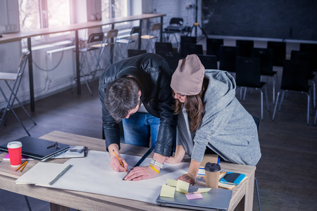 architect drawing: Team of architects people drawing construction project on desk. business workflow. office concept. Working environment with laptop, coffee, notepads and stationery. Stock Photo