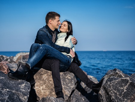 emotional couple sitting on the rocks