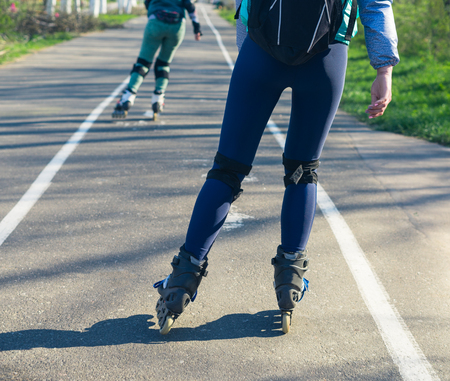roller blade: Two girls on roller skates ride along the road next to each other