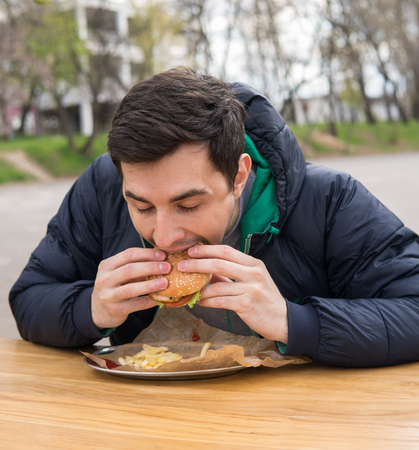 man eating very tasty burger in street food cafe Stock Photo