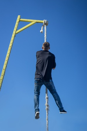 Young Athlete climbing up the Fitness rope