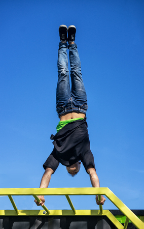 Young Athlete doing a Hand Stand On Parallel Bars In An Outdoor Gym