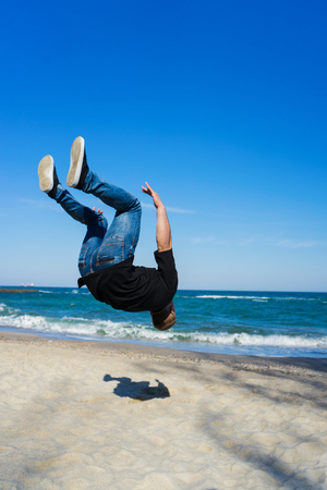somersault: young parkour man doing flip or somersault